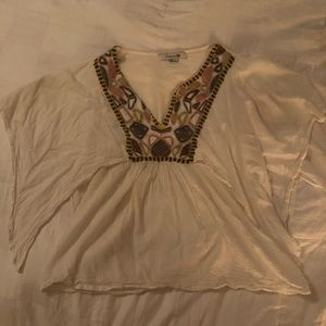 Flared arms top with beads.